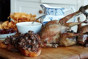 cooked young grouse on wooden board